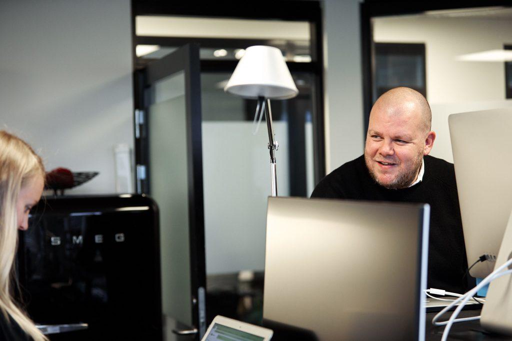 En mann på et kontor som smiler og ler