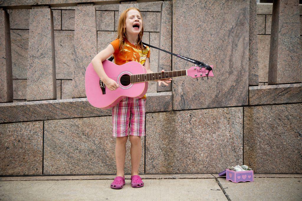 Jente med rosa gitar som synger på gata