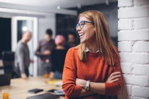 Bilde av dame i orange genser i kontorlandskap