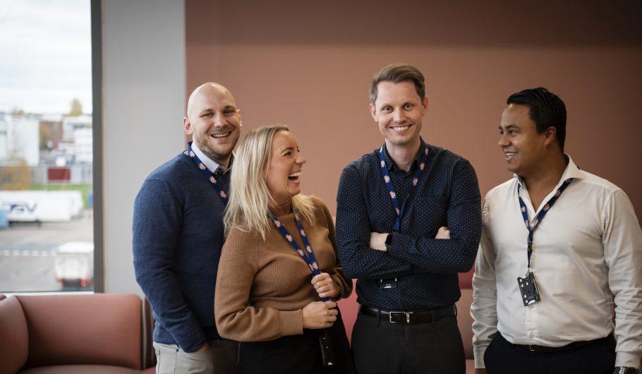 Bilde av fire smilende ansatte i Tine