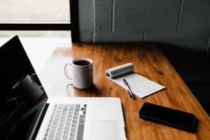 Arbeidsbord med skriveblokk, kaffe og Mac
