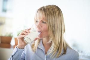 Blond dame som drikker et glass med melk.
