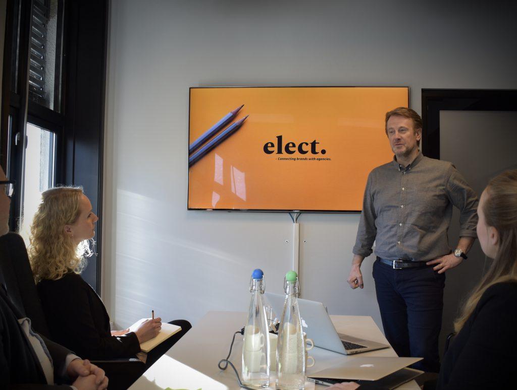 Mann holder presentasjon av Elect