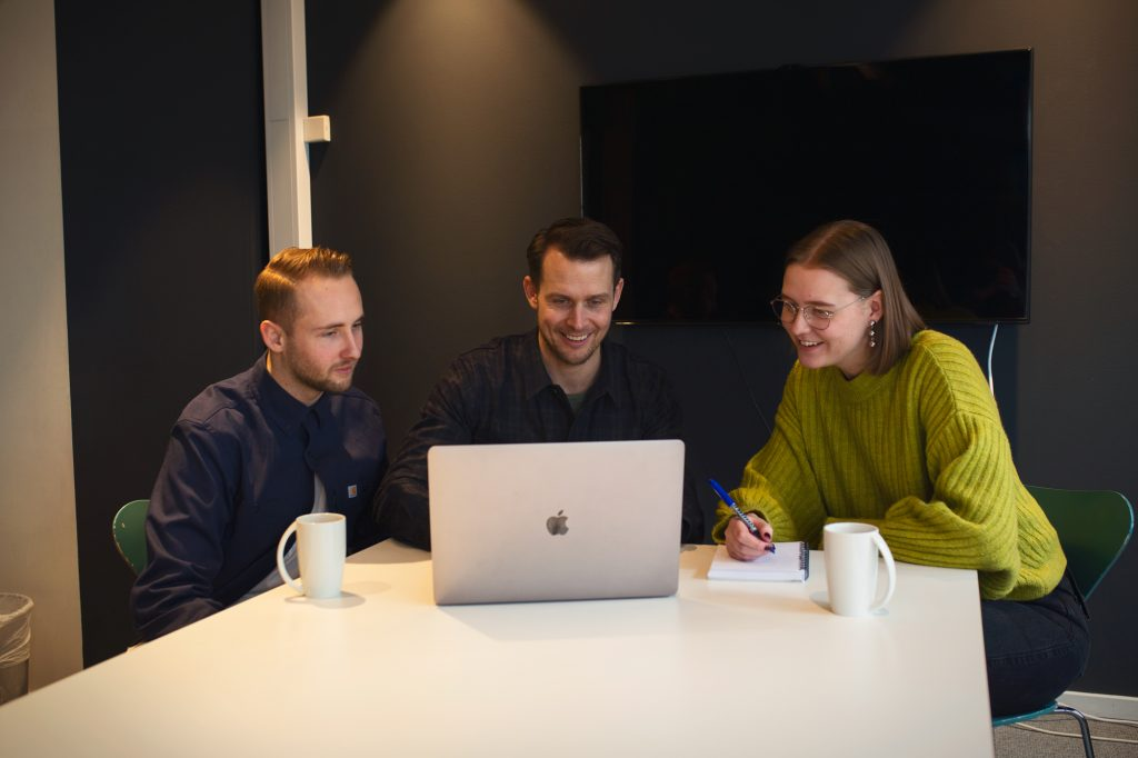 Tre kollegaer som sitter rundt en mac og jobber i NORD DDB.
