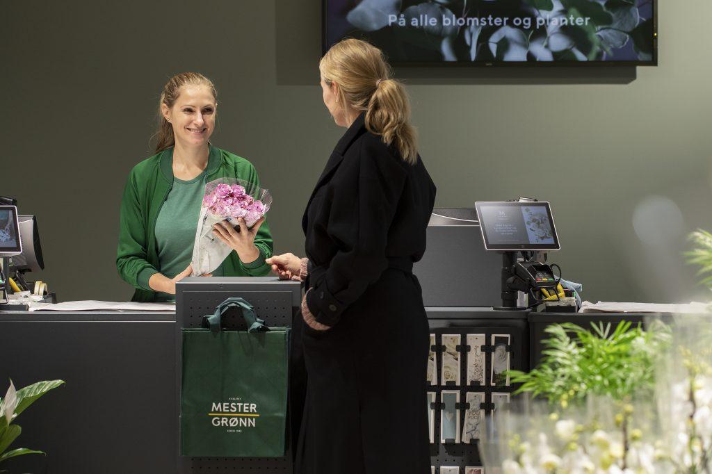 En kvinnelig kunde handler blomster av en smilende kassadame hos Mester Grønn