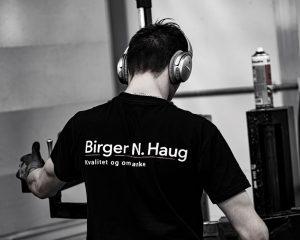 """Illustrasjonsbilde av ryggen til mann med teksten Birger N. Haug """"kvalitet og omtanke""""."""