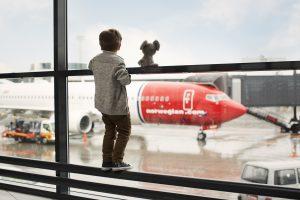 Gutt på flyplass ser på et Norwegian-fly på gaten